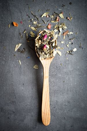 gunpowder tea: Green Sencha tea flavored with flowers and zest in a wooden spoon on a dark background Stock Photo