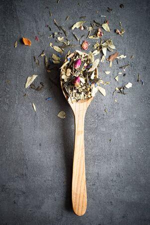 rosas naranjas: T� Sencha verde aromatizado con flores y la ralladura de una cuchara de madera sobre un fondo oscuro Foto de archivo