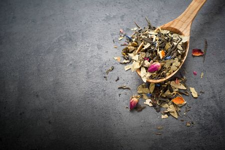 sencha: Green Sencha tea flavored with flowers and zest in a wooden spoon on a dark background Stock Photo