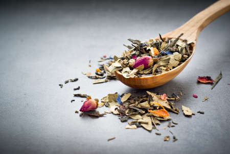 sencha tea: Green Sencha tea flavored with flowers and zest in a wooden spoon on a dark background Stock Photo