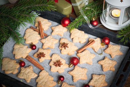 Christmas cookies on a baking sheet with spices and decorations.