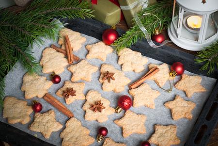 galletas: galletas de Navidad en una bandeja para hornear con las especias y las decoraciones.