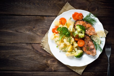 Grilled salmon steak garnished with vegetables. Top view, style rustic. Stockfoto
