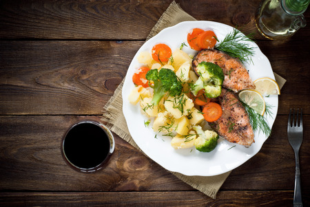 Grilled salmon steak garnished with vegetables. Top view, style rustic. Archivio Fotografico