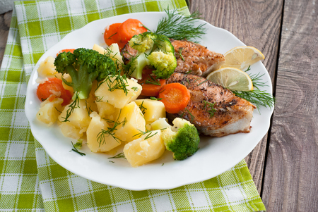 fish plate: Grilled salmon steak garnished with vegetables. Top view, style rustic. Stock Photo
