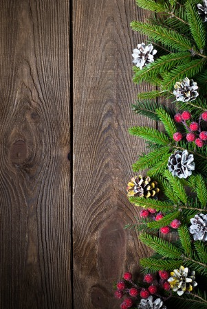 brunches: Christmas background with tir tree brunches and decorations at dark wooden table. Top view, copy space.