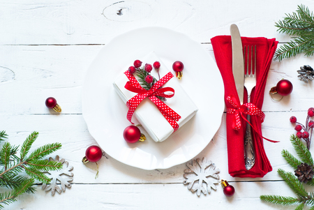 Christmas table setting with christmas decorations and gift at white table. Top view. Archivio Fotografico
