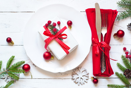 dining set: Christmas table setting with christmas decorations and gift at white table. Top view. Stock Photo