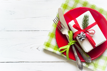 Christmas table setting with gift at white table. Top view, copyspace. Stock Photo