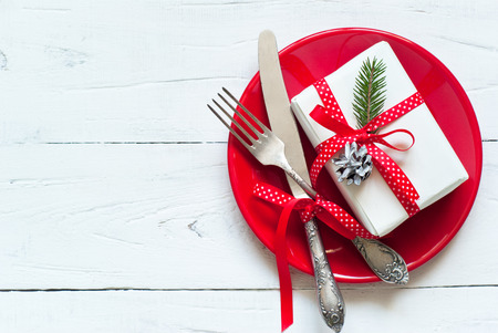 Christmas table setting with gift at white table. Top view, copyspace. Stockfoto