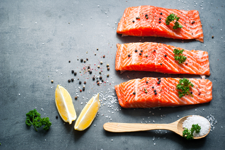 Raw Fillet of salmon with sea salt and pepper. Fresh fish. Top view, copy space. Food background.