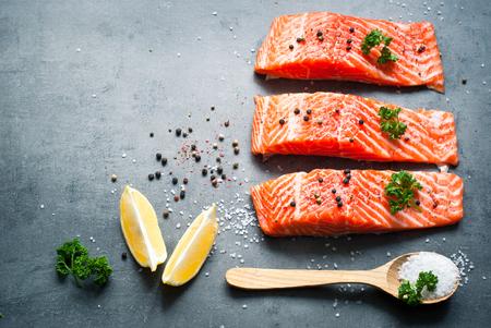 海の塩とコショウとサーモンの生の切り身。新鮮な魚。上面図、空間をコピーします。食品の背景。