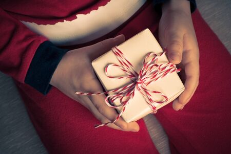 christmas symbol: Little boy dressed as Santa holds a gift for Christmas in his hands.