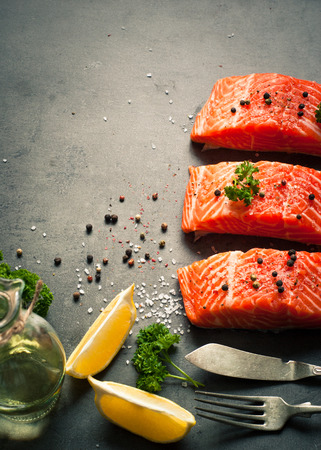 Raw Fillet of salmon with sea salt and pepper. Fresh fish. Top view, copy space. Stock Photo