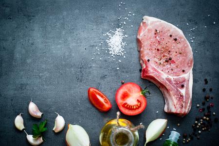 Rauw varkensvlees op een donker grijze oppervlak en ingrediënten voor het koken. Voedsel achtergrond met een kopie ruimte. Stockfoto
