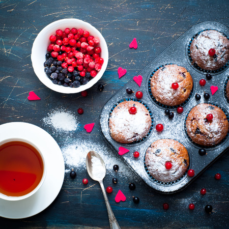 muffin: Muffins with red and black currant sprinkled with powdered sugar. Decorated to Valentines day. Stock Photo