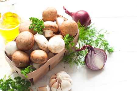 agaricus: Basket with mushrooms and ingredients for cooking at white wooden table. Space for text. Stock Photo