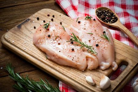 carne de pollo: filete de pollo con especias y el romero en una superficie de madera oscura. Estilo rústico.