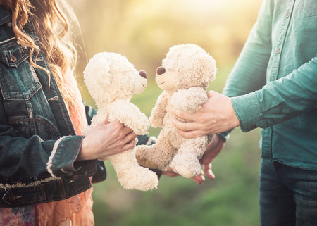 Young couple holding two teddy bears in his hands. Concept of love and tenderness.