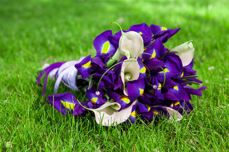 purple irises: Bouquet of purple irises and white calla lilies in the grass