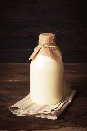 milkman: Old fashioned Bottle with milk at wooden table.