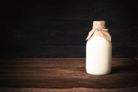 昔ながらの木製のテーブルで牛乳瓶。テキストのためのスペース。