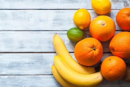 Fresh citrus fruits - lime, lemon, orange, grapefruit and banana at wooden table. Top view.