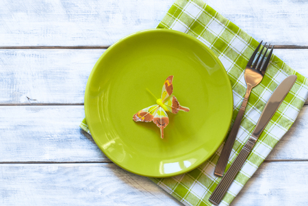 butterfly knife: Spring table setting with green plate over wooden table background. View from above with copy space