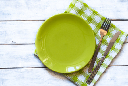 Spring table setting with green plate over wooden table background. View from above with copy space