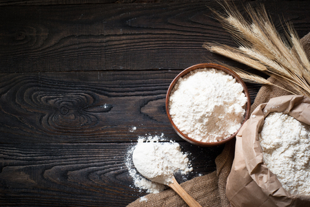 Flour in a wooden bowl, paper bag and spoon. Top view, space for text.