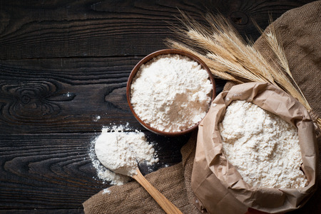 bawl: Flour in a wooden bowl, paper bag and spoon. Top view, space for text.