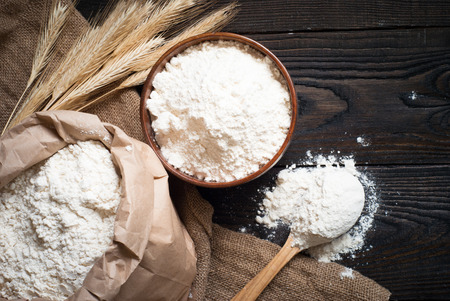 flour: Flour in a wooden bowl, paper bag and spoon. Top view, space for text.