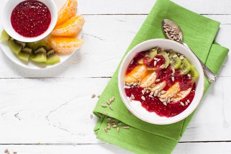 bawl: Dessert with sour cream, orange, kiwi, raspberry jam and seeds. Healthy food or diet. Stock Photo