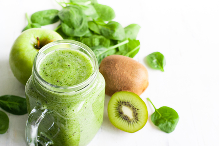 spring green: Healthy green smoothie and ingredients on white - spinach, apple and kiwi. Stock Photo