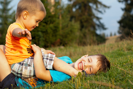 greeen: Two little boy playing in the grass in sunny summer day.