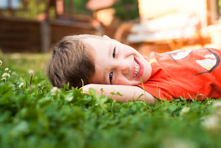 greeen: Smiling little boy in the grass in sunny summer day. Stock Photo