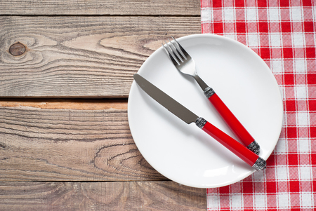 copy: Table setting with a plate, cutlery and napkin in red and white colors. View from above with copy space