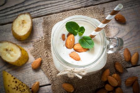 Shake from almond milk, banana and coconut in a mason mug. Dairy free.