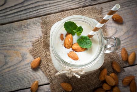アーモンド ミルク、バナナ、メイソン マグカップにココナッツから振る。乳製品フリー。 写真素材