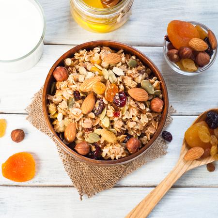 Granola flocons de céréales avec des fruits secs, de noix et de miel dans un bol en bois.