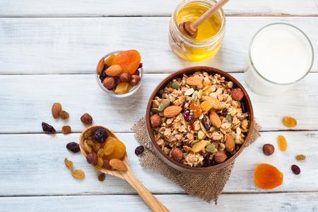 frutas deshidratadas: copos de cereales de granola con frutas secas, frutos secos y miel en un tazón de madera.