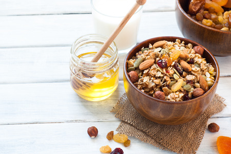 Granola cereal flakes with dried fruit, nuts and honey in a wooden bowl. Stock Photo