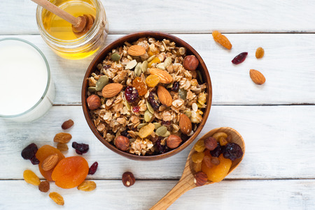 cereal bowl: Granola cereal flakes with dried fruit, nuts and honey in a wooden bowl. Stock Photo