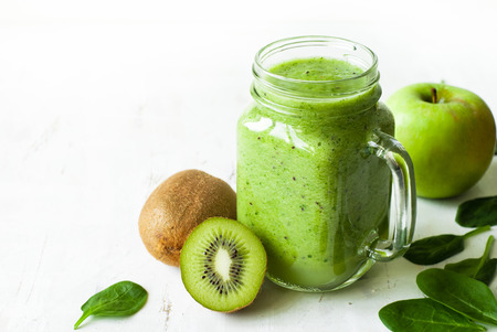 Healthy green smoothie and ingredients on white - spinach, apple and kiwi. Superfood, detox and  healthy food.