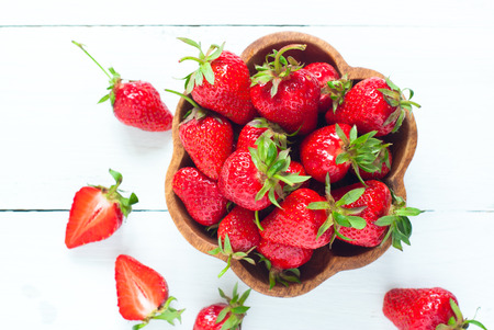 woden: Fresh strawberries in woden bowl at white wooden table.