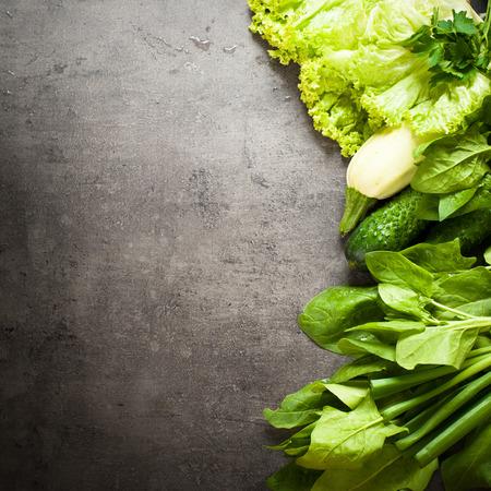 Los vegetales verdes en el fondo de la pizarra con el espacio para el texto. La alimentación saludable y el concepto de dieta. Fondo de la comida vegana.