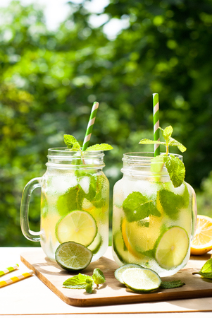 Summer drink lemonade mojito with lime, lemon  and mint in mason jar outdoor.