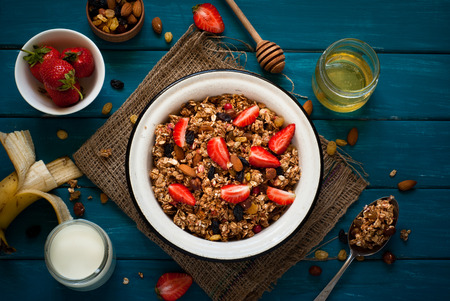 bawl: Granola. Granola with yogurt, honey and berries on blue wooden table. Stock Photo