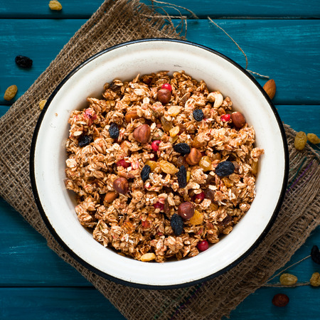 bawl: Granola and ingredients. Granola with nuts and raisins on blue wooden table. Stock Photo