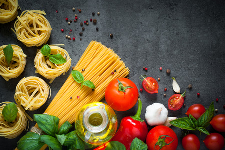 copyspace: Pasta ingredients. Ingredients for cooking Italian pasta - spaghetti, tomatoes, basil, oil and garlic. Italian food. Top view with space for text. Stock Photo
